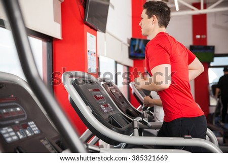 Profile view of a young athletic man jogging on a treadmill at the gym - stock photo