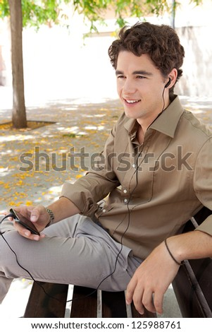 Profile view of a young businessman using his smart phone and a hands free set to make a call while sitting on a bench in the city. - stock photo