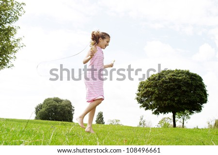 Profile view of a young girl playing skipping rope in the park, smiling. - stock photo