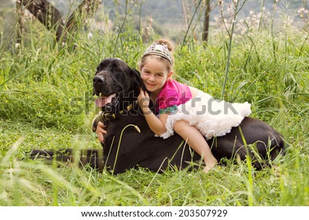 Profile view of a young girl wearing a pink fancy dress with crown, sitting on her dogs back enjoying a sunny holiday in a green park field, hugging and smiling. Active family with pets, lifestyle. - stock photo