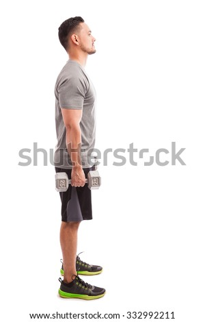 Profile view of a young man in sporty outfit about to lift some weights on a white background - stock photo