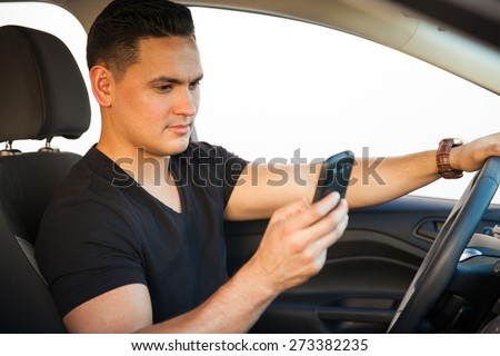 Profile view of a young man looking at his smartphone while he drives a car - stock photo
