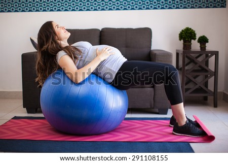 Profile view of a young pregnant woman stretching and supporting her back on a stability ball at home - stock photo