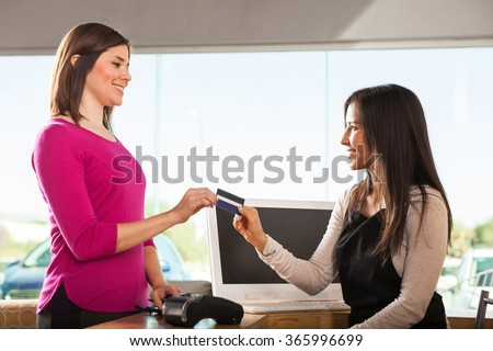 Profile view of a young woman paying with a credit card at a cash register in a store - stock photo