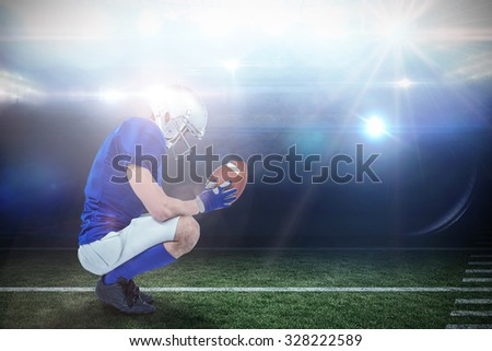 Profile view of American football player in attack stance against american football arena - stock photo