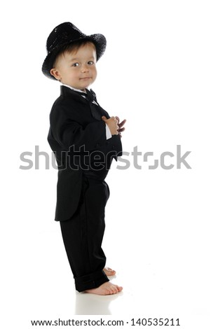 Profile view of an adorable toddler happily looking back at the camera in his black sequined fedora, bow tie and tailed tuxedo.  On a white background.