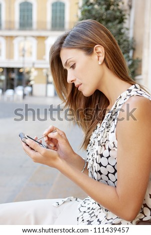 Profile view of an attractive businesswoman sitting down in a classic city's square using a tablet smart phone.