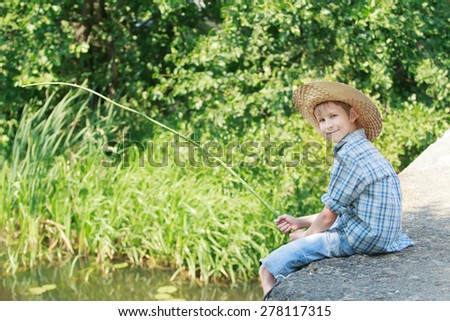Profile view of angling boy with wooden rustic fishing rod is sitting on concrete bridge  - stock photo