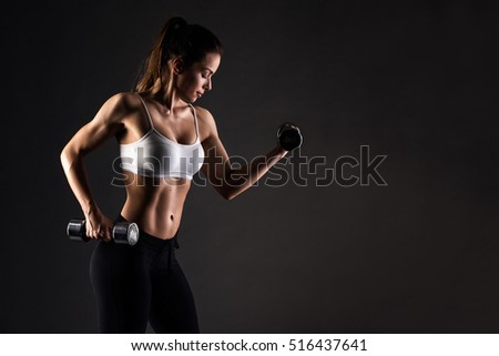 Profile view of beautiful athletic girl exercising. Young woman with muscular body. Fitness concept