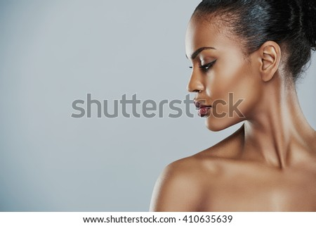 Profile view of beautiful grinning African bare shouldered female with short hair looking sideways over gray background - stock photo