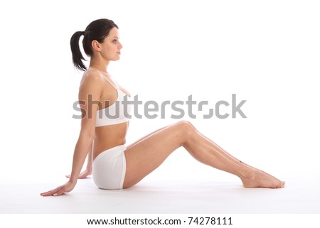Profile view of beautiful healthy young woman wearing white sports underwear, sitting on floor with knees raised. - stock photo