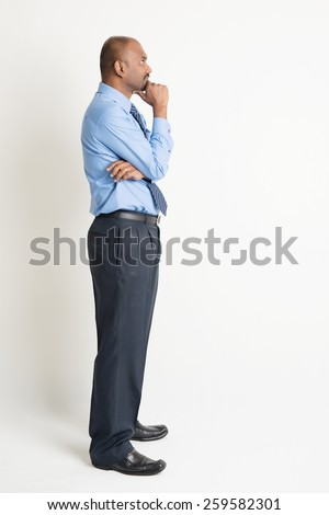 Profile view of full body Indian businessman hand on chin looking up at blank copy space, standing on plain background with shadow - stock photo
