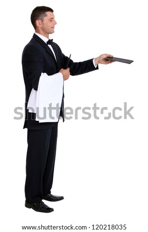 Profile view of male waiter holding out menu - stock photo