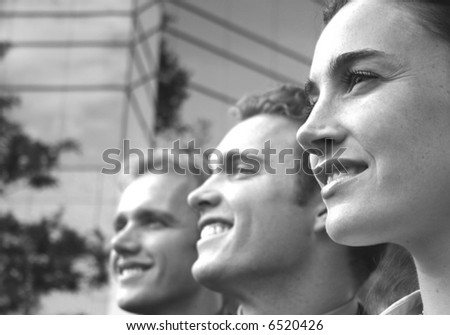 profile view of one female two males in a row looking away smiling in front of blue building structure - stock photo