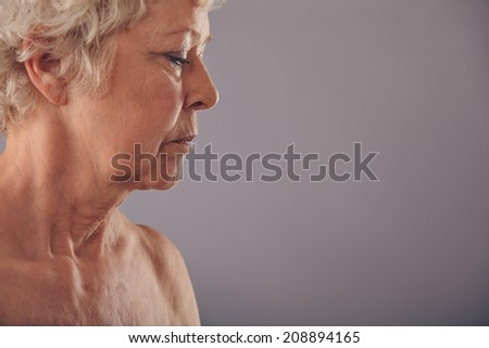 Profile view of senior woman face against grey background, Naked mature woman looking down. - stock photo