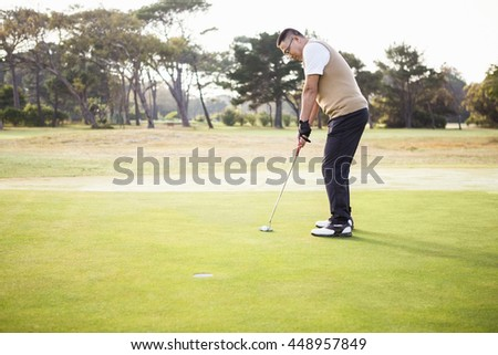 Profile view of sportsman playing golf on a field - stock photo