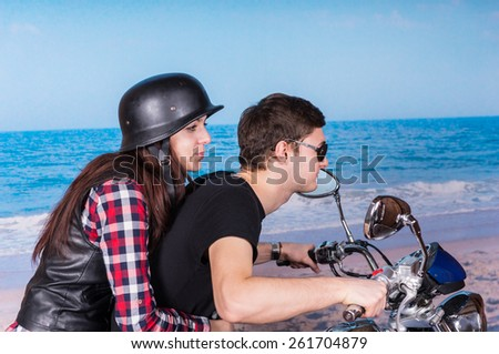 Profile View of Young Couple Riding Two Up on Motorcycle at Beach - stock photo