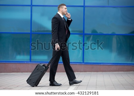 Profile view portrait of cheerful young man on business trip walking with his luggage while talking on smartphone in front of modern glass building outdoors. Travelling guy making call. Copy space - stock photo