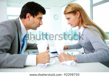 Profiles of angry employees with papers looking at each other strictly - stock photo