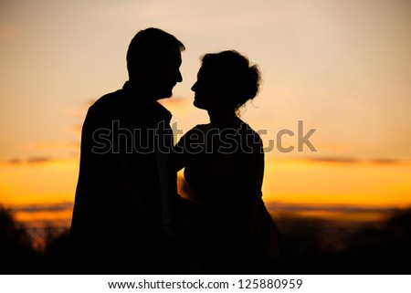 Profiles of romantic couple looking at each other on sunset back light - stock photo