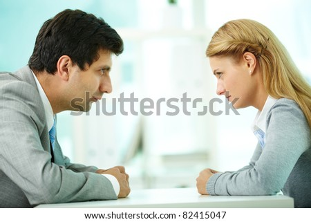 Profiles of serious employees looking at each other - stock photo
