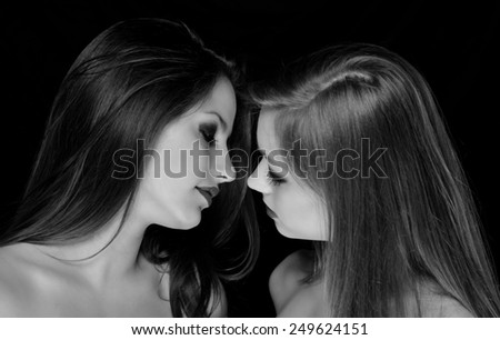 Profiles of two beautiful girls being intimate isolated on black background. Black and white photo. - stock photo