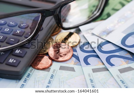 Profit concept. Eyeglasses and calculator on euro currency background