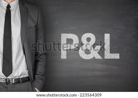Profit & loss statement on black blackboard with businessman - stock photo