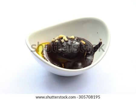 Profiterole in the bowl with chocolate and nuts