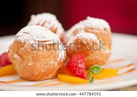 profiteroles from cream and condensed milk decorated with strawberry and peach - stock photo