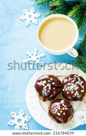 profiteroles with chocolate icing and colored powder and cup of coffee on a blue background. tinting. selective focus on the left top profiterole - stock photo