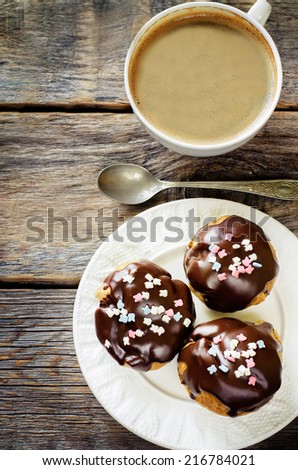 profiteroles with chocolate icing and colored powder and cup of coffee on a dark wood background. tinting. selective focus on the middle of top profiterole - stock photo