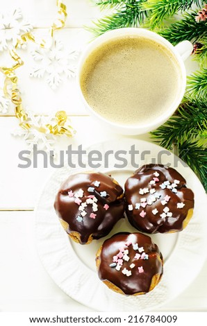 profiteroles with chocolate icing and colored powder and cup of coffee on a light wood background. tinting. selective focus on the middle of left profiterole - stock photo