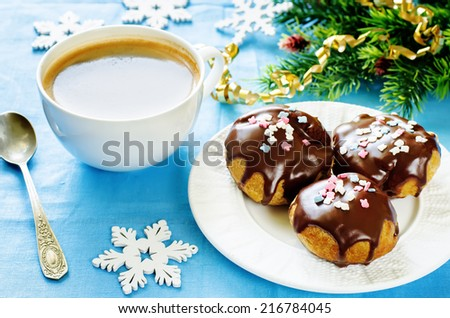 profiteroles with chocolate icing and colored powder on a blue background. tinting. selective focus on the top middle front profiteroles - stock photo