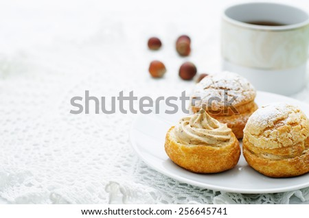 profiteroles with cream with praline on a white background. tinting. selective focus - stock photo