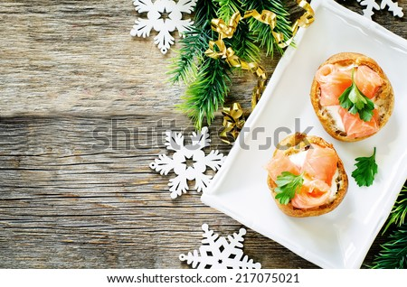 profiteroles with salmon and cream cheese on a dark wood background. tinting. selective focus on parsley on the top profiterole - stock photo