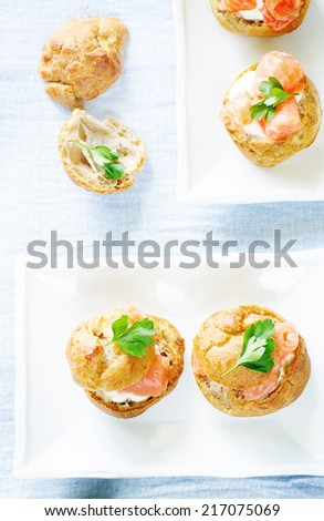 profiteroles with salmon and cream cheese on a light blue background. tinting. selective focus on parsley on the left bottom profiterole - stock photo