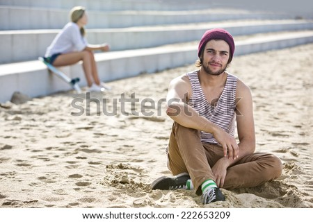 Profound looking dude, sitting in the sand on a beach with a woman sitting on concrete steps in the background. - stock photo