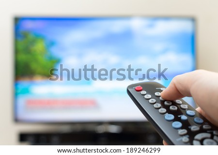 Program switching or button pressing on TV remote control - stock photo