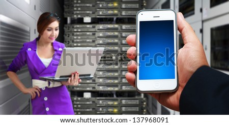 Programmer and smart phone in server room  - stock photo