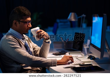 Programmer drinking coffee and computing at night, side view - stock photo