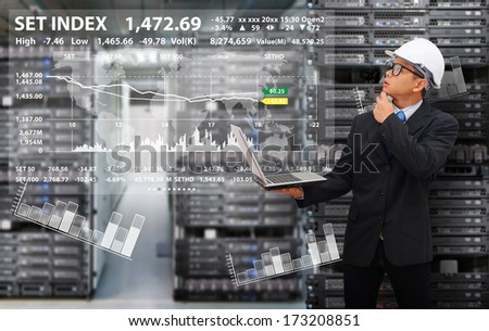 Programmer in data center room and looking to graph report - stock photo