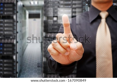 Programmer in data center room press on power button - stock photo