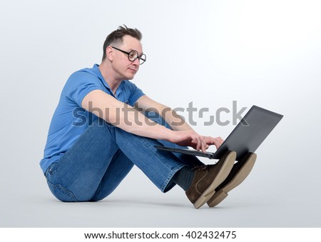 Programmer in glasses working on a laptop and sitting the floor