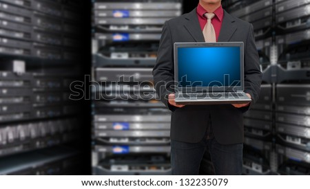 Programmer with laptop in data center room - stock photo