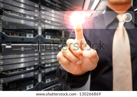 Programmer with power button in data center room - stock photo