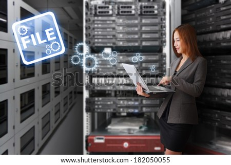 Programmer working with laptop in server room