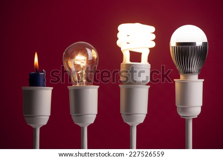 Progress of lighting displayed with candle, tungsten, fluorescent and LED bulb - stock photo