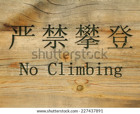 prohibition sign in chinese and english : no climbing  - stock photo