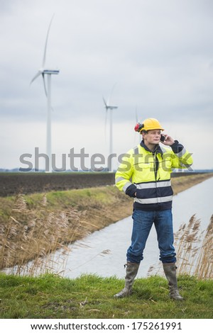 Project developer calling on the phone with business clients standing in a green environment - stock photo